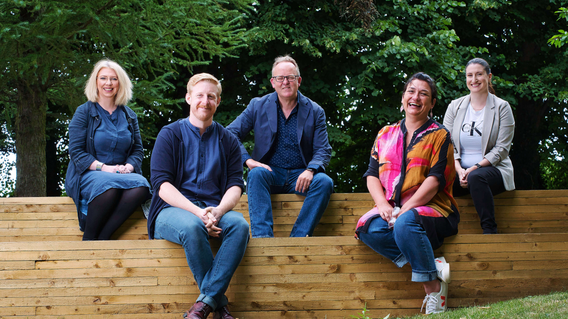 Una Nic Eoin, Michael Patrick, Jimmy Fay, Emma Jordan, Natalie Murphy sitting in the outdoor amphitheatre at the Lyric Theatre