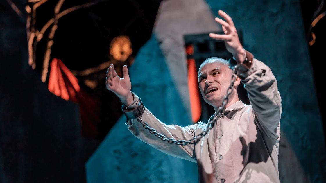 A still from Lyric Drama Studio production, Dracula featuring a man holding his arms aloft with his wrists in shackles.