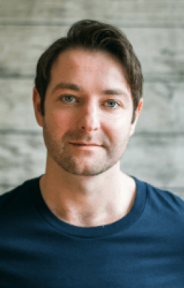 Patrick McBrearty Headshot  - Man with short brunette hair and slight stubble wearing a blue top on a background of wood panelling