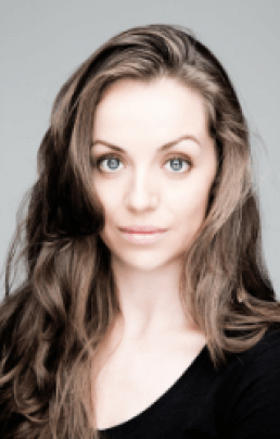 Liz Fitzgibbon headshot - Brunette female with her hair down, wearing a black top on a grey background