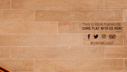 A brick wall backdrop featuring a quote from Brian Friel, four social media icons and the hashtag #LyricBelfast written in black.