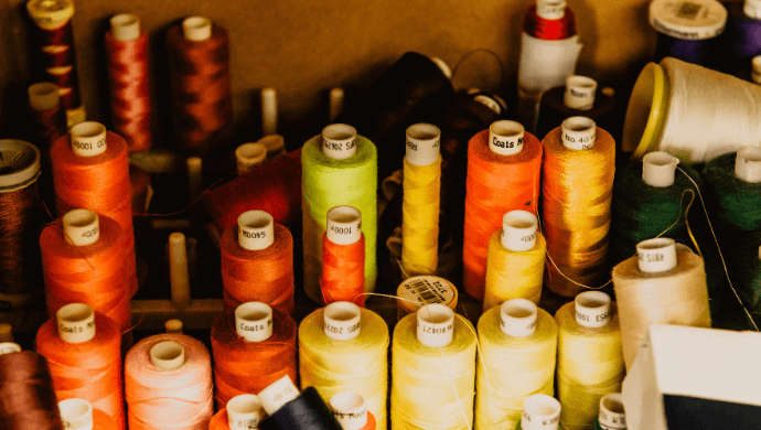 A variety of different coloured spools of thread.