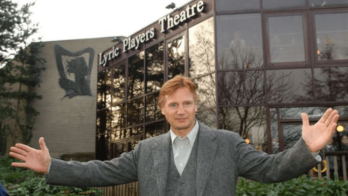 Actor Liam Neeson stands outside the old Lyric Theatre building.
