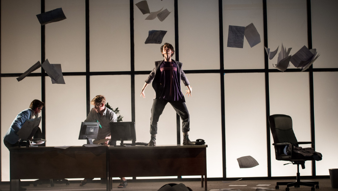 A production still from the Lyric, showing a stylistic shot of three actors, one standing a desk and two others at computers with papers flying around them.