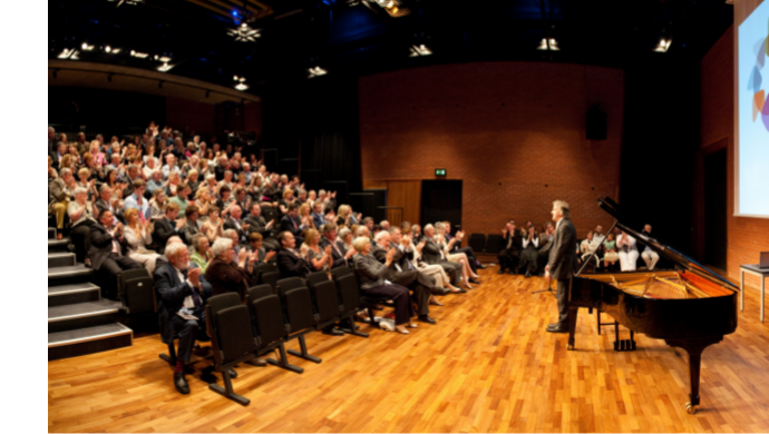 An audience applaud a performer standing on stage beside a grand piano in the Naughton Studio at the Lyric.