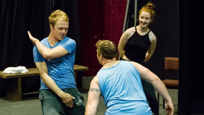 Three people rehearse a scene.
