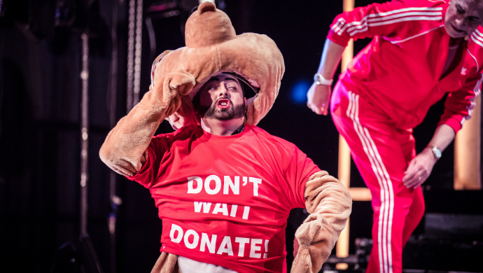 A man on stage at the Lyric lifts the head of his furry animal costume to reveal his face, wearing a 'Don't Wait Donate' red t-shirt over his costume.