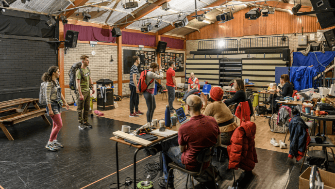 A group of actors rehearsing in a rehearsal space filled with props and tables, watched by six other people in various seats.