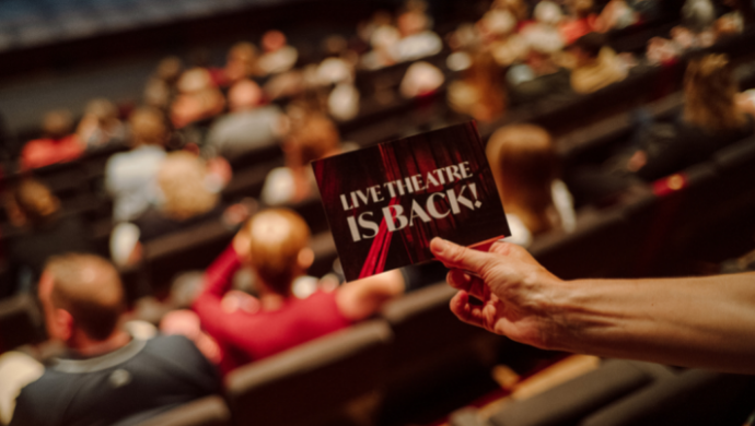 A close up of a card reading 'Live Theatre is Back!' being held in front of audience members sitting in the auditorium of the Main Stage.