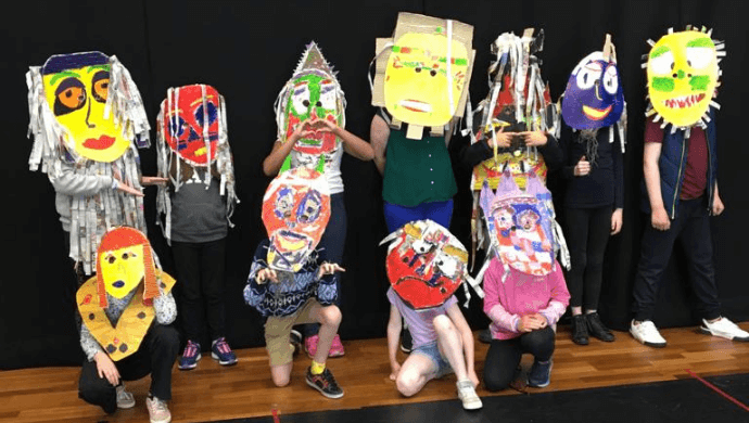 A group of young people wearing different large masks over their faces.