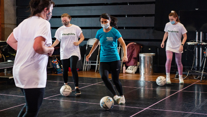 A group of women practicing dribbling with footballs in the rehearsal room of the Lyric Theatre.