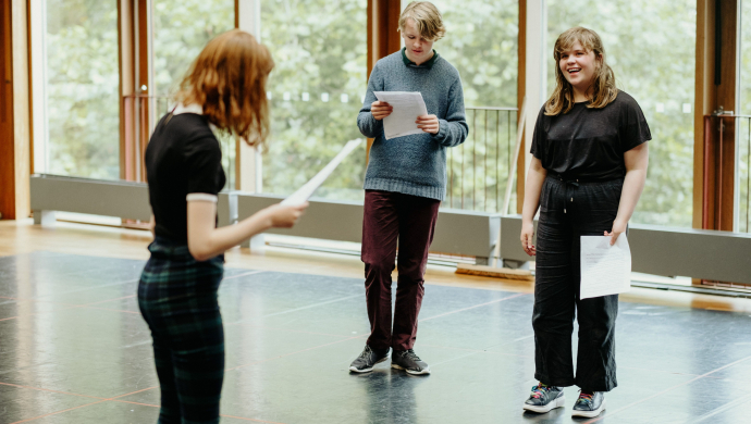 Three young people rehearse with scripts during a drama class at the Lyric Theatre.